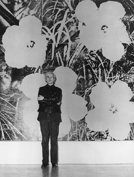 Andy Warhol standing in front of one of his large silk screen paintings of flowers, 15 January 1973. Image: Evening Standard/Getty Images.