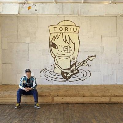 The artist, Yoshitomo Nara, in front of his work. Photography by Ryoichi Kawajiri © Yoshitomo Nara