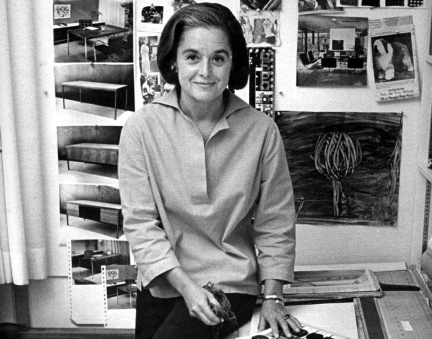 Portrait of American architect and furniture designer Florence Knoll Bassett as she sits on the edge of a table with a book of fabric swatches in front of her, 1961.  Image: Ray Fisher/The LIFE Images Collection, Getty Images.